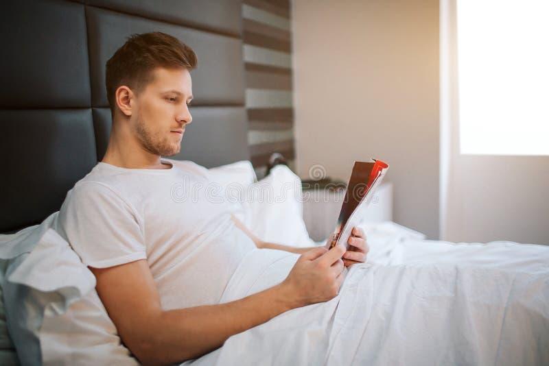 Junger gut aussehender Mann las herein Schlafzimmer konzentriert Tageslicht Er bedeckte mit weißer Decke stockbild