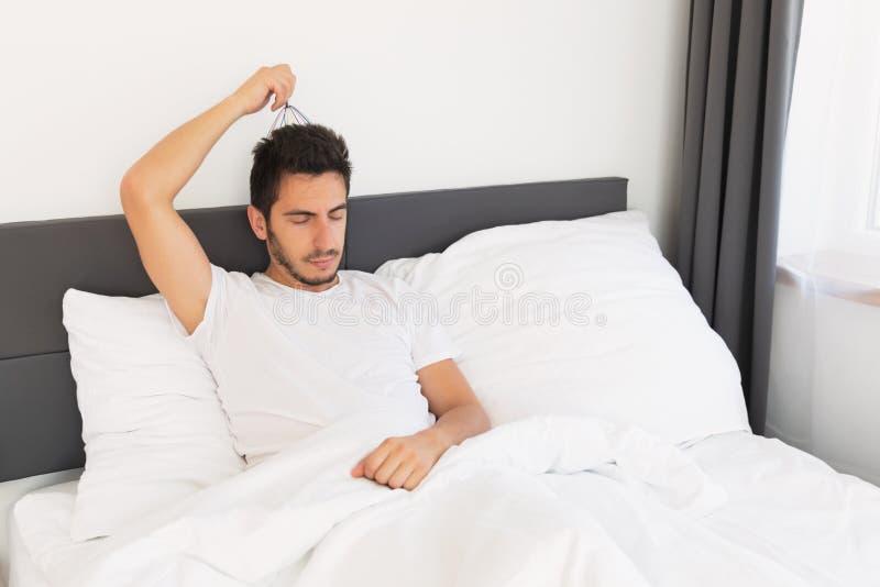 Junger gut aussehender Mann mit einem Bart sitzt in seinem Bett lizenzfreies stockfoto