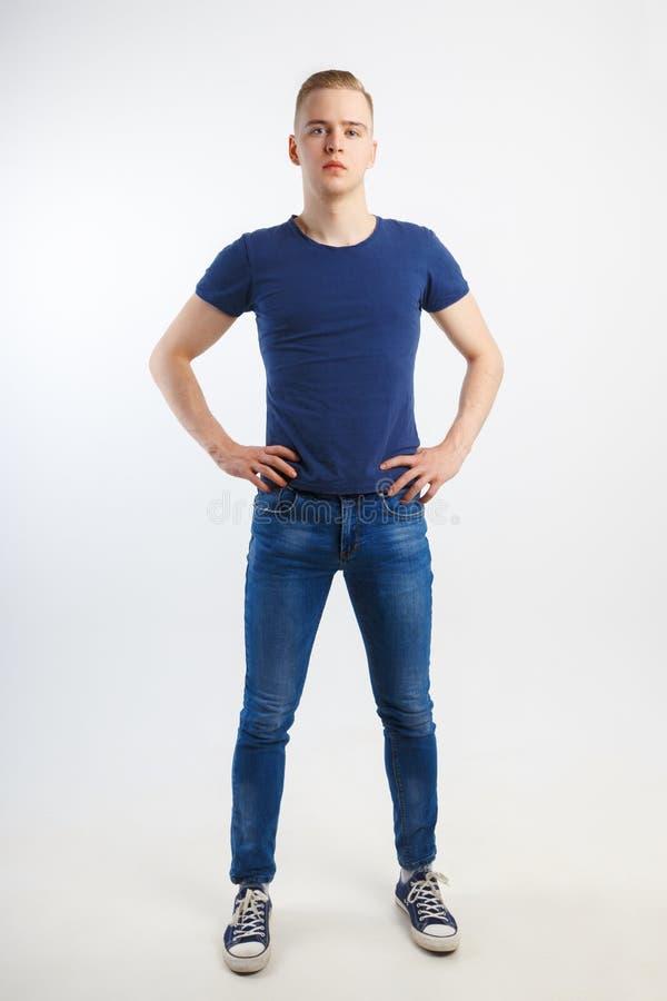 Junger gutaussehender Mann in den blauen Hemd- und Jeanshaltungen stockbild