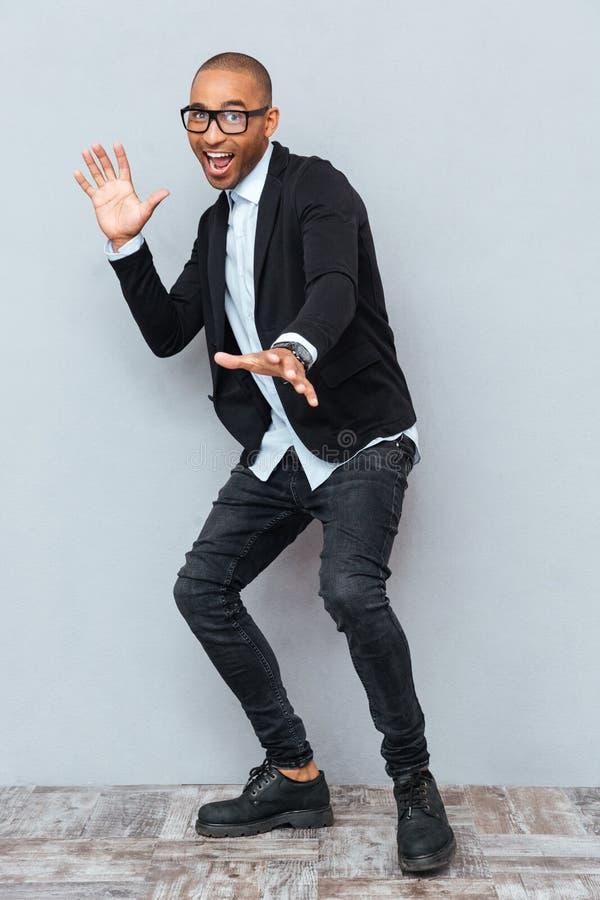 Junger gutaussehender Mann, der über grauen Hintergrund tanzt stockfoto