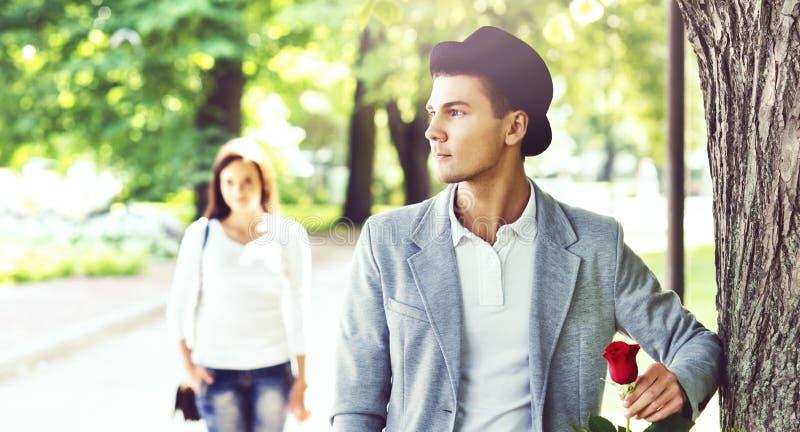 Junger gutaussehender Mann, der auf seine Freundin im Park wartet lizenzfreie stockfotos