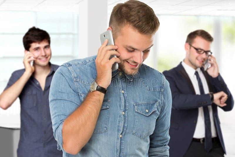 Junger gutaussehender Mann, der Handy verwendet, um zu nennen lizenzfreies stockbild