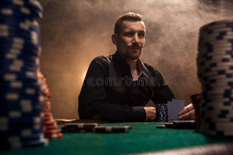Junger gutaussehender Mann, der hinter Pokertabelle mit Karten und Chips sitzt lizenzfreie stockfotografie
