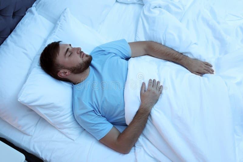 Junger gutaussehender Mann, der im Bett nachts schläft stockbilder