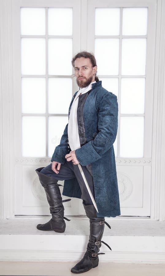 Junger gutaussehender Mann in der mittelalterlichen Kleidung mit Klingenstellung lizenzfreies stockbild