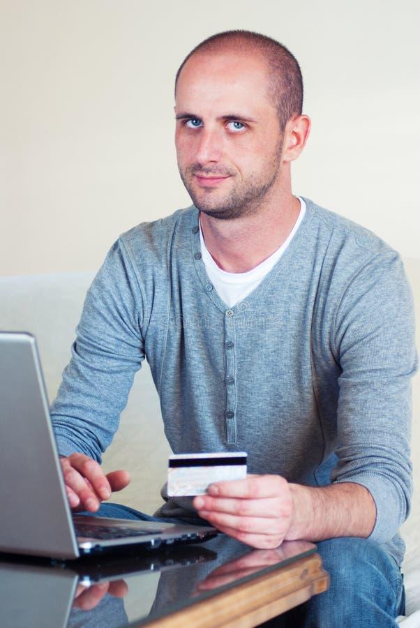 Junger gutaussehender Mann, der online kauft stockfotos