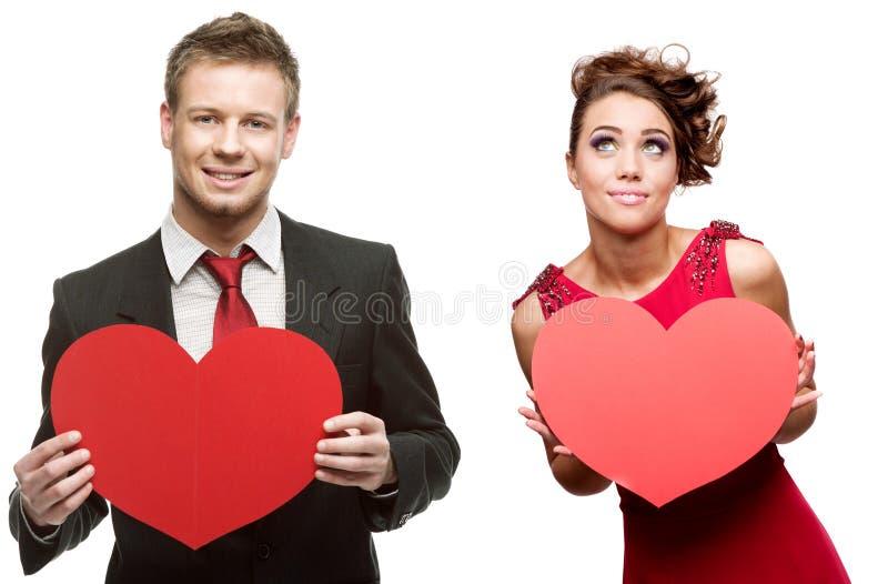 Junger gutaussehender Mann, der rotes Herz halten und nette Frau auf Weiß lizenzfreie stockfotografie
