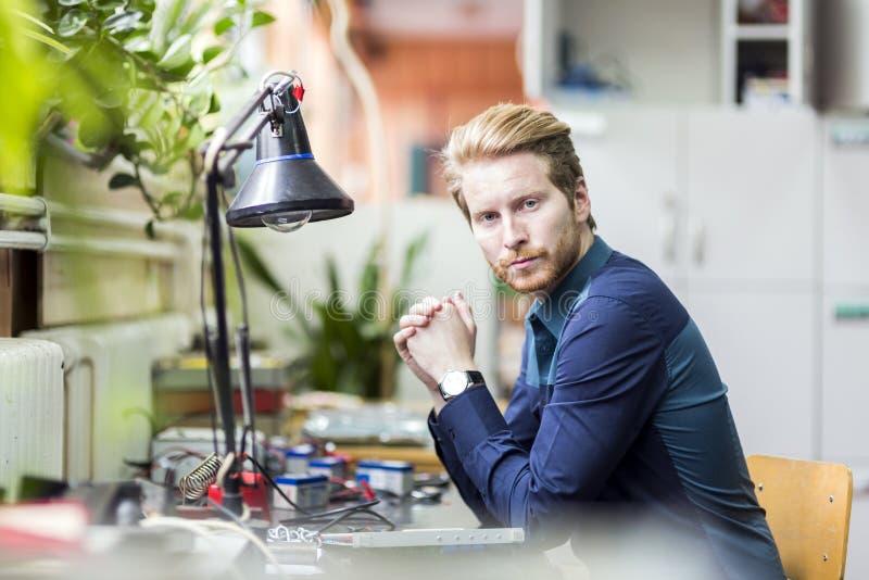 Junger gutaussehender Mann, der wie man die Leiterplatte denkt, lötet lizenzfreie stockbilder