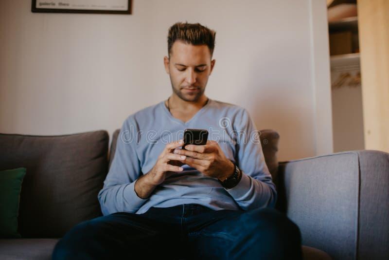 Junger gutaussehender Mann, der zu Hause auf Sofa sitzt und Handy verwendet Männer, die Smartphonehände halten und Textnachricht  lizenzfreie stockfotografie