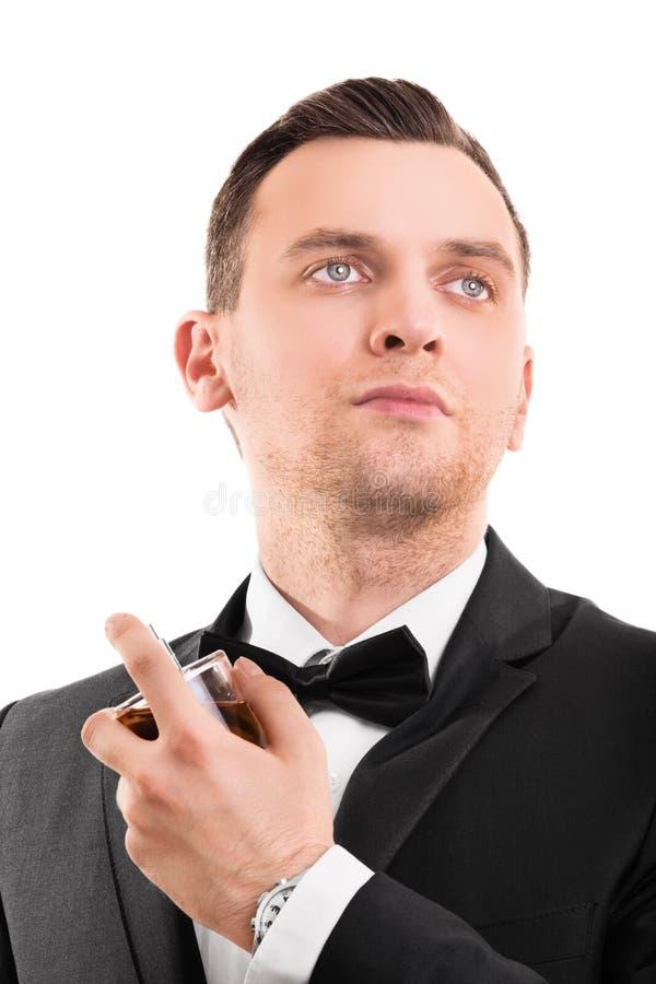 Junger gutaussehender Mann in einer Klage unter Verwendung eines Parfüms stockbild