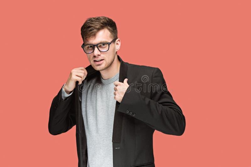 Junger gutaussehender Mann im schwarzen Anzug und in den Gläsern lokalisiert auf rotem Hintergrund stockfotografie