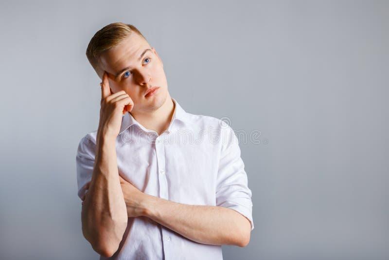 Junger gutaussehender Mann im weißen Hemd berührt seinen Kopf lizenzfreie stockfotografie