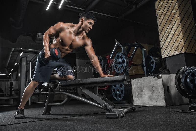 Junger gutaussehender Mann mit dem asiatischen Mannhandeln der großen Muskeln übt uns aus lizenzfreie stockfotografie