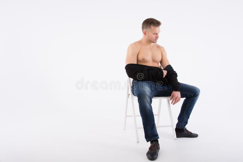 Junger gutaussehender Mann steht still Der hemdlose Kerl sitzt auf der Couch Muskulös und sexy lizenzfreie stockfotos