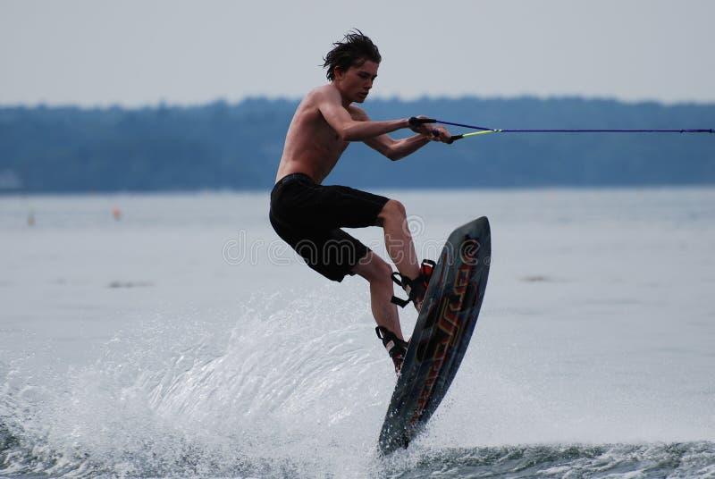 Junger Guy Wakeboarding Catching Big Air über dem Wasser lizenzfreie stockfotos