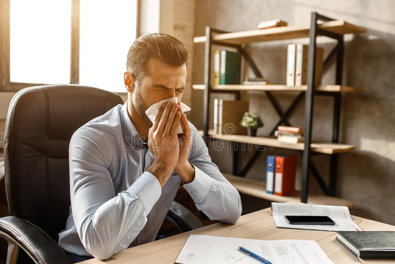 Junger hübscher Geschäftsmann bei Tisch sitzen und in seinem eigenen Büro niesen Er bedeckt Nase mit weißer Serviette Kranker Ker lizenzfreies stockbild