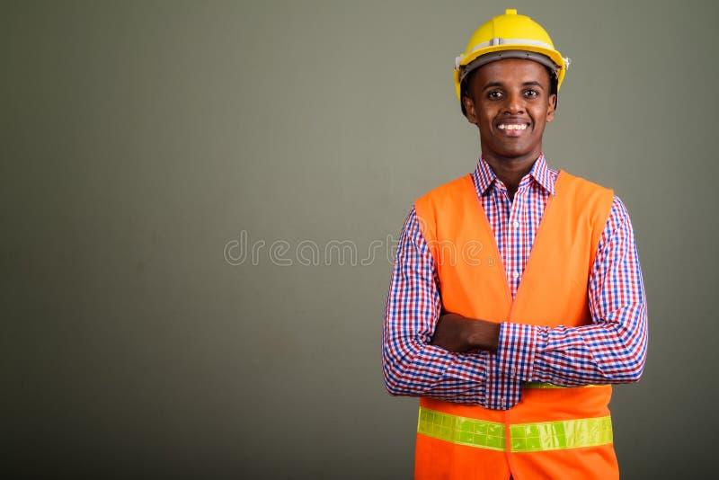 Junger hübscher afrikanischer Mannbauarbeiter gegen farbiges b lizenzfreie stockfotos