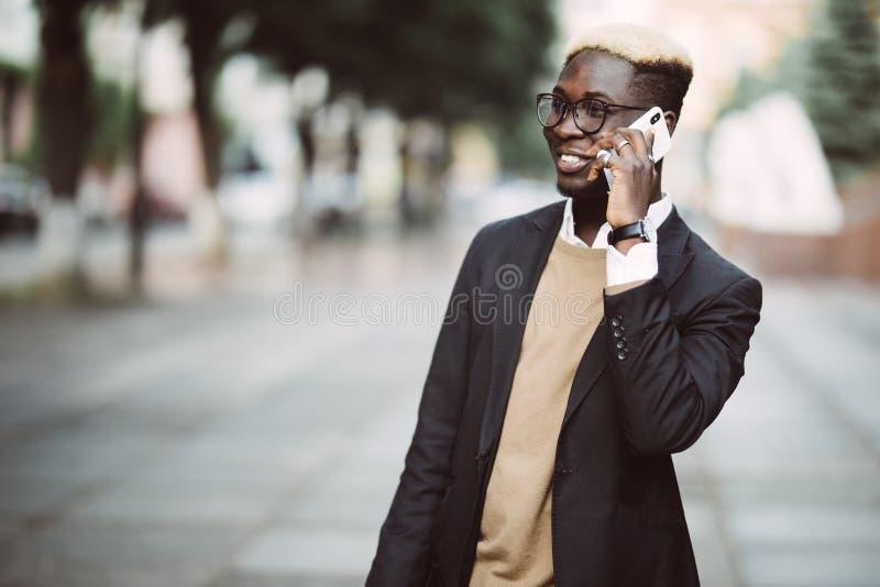 Junger hübscher afroer-amerikanisch Geschäftsmann, der draußen auf seinem Mobiltelefon in der Straße spricht lizenzfreie stockfotografie