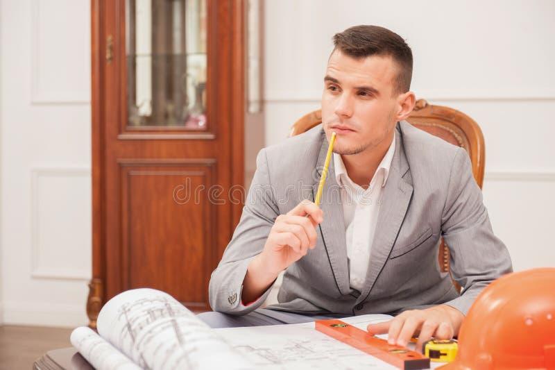 Junger hübscher Architekteningenieur, der an arbeitet stockfotos
