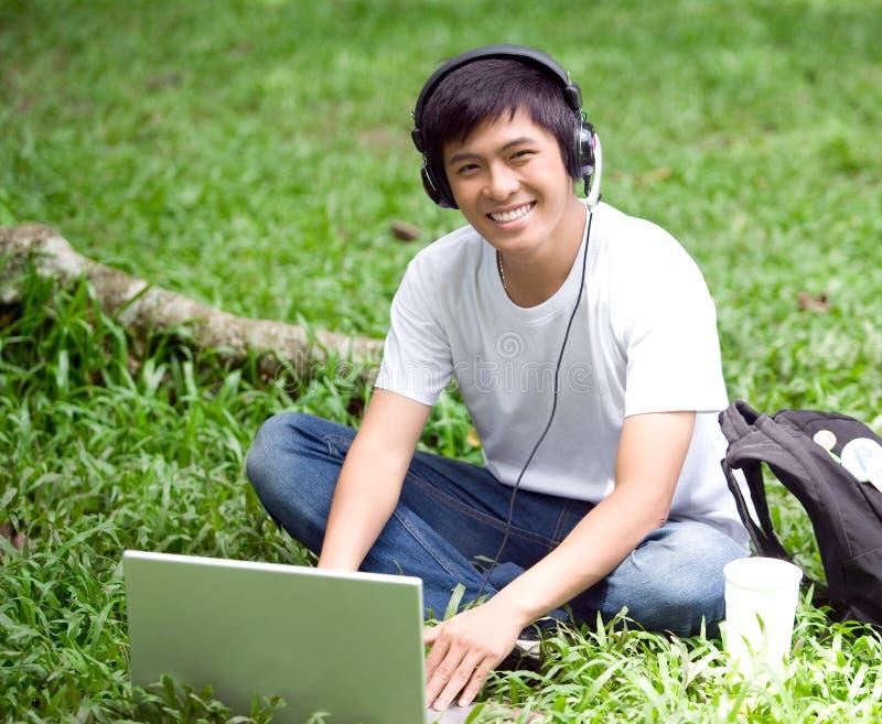 Junger hübscher asiatischer Student mit Laptop und Lächeln in im Freien lizenzfreie stockfotografie