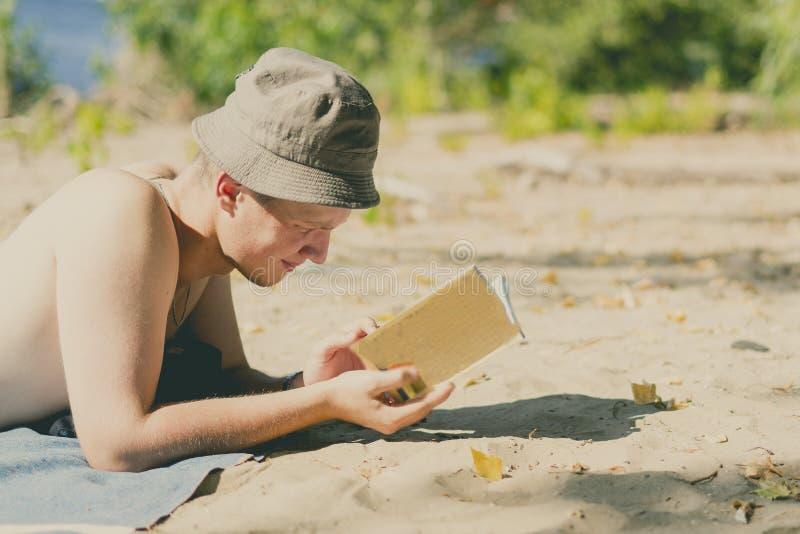 Junger hübscher attraktiver Mann in Panama, das auf sandigem Himmelsstrand liegt und ein Buch an einem Sommertag liest lizenzfreies stockfoto