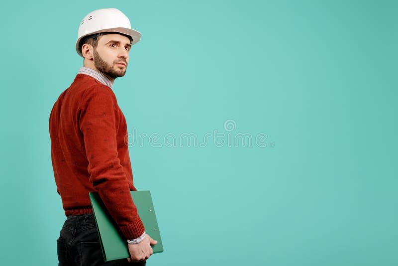 Junger hübscher bärtiger Ingenieur- oder Erbauermann in der zufälligen Ausstattung, die grünes Klemmbrett über cyan-blauem Hinter stockfotografie