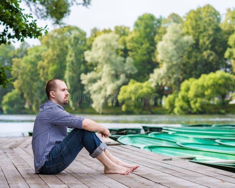 Junger hübscher bärtiger Mann, der auf hölzernem Pier sitzt  stockfotografie