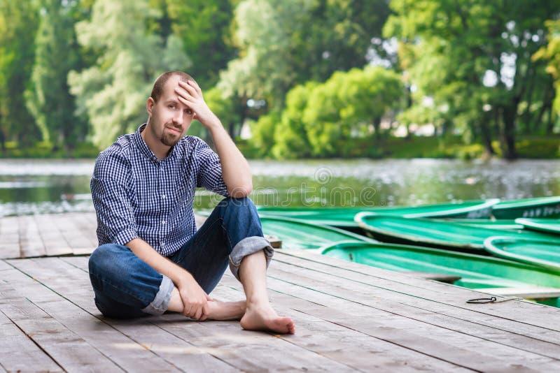 Junger hübscher bärtiger Mann, der auf hölzernem Pier am Sommertag sitzt lizenzfreies stockfoto