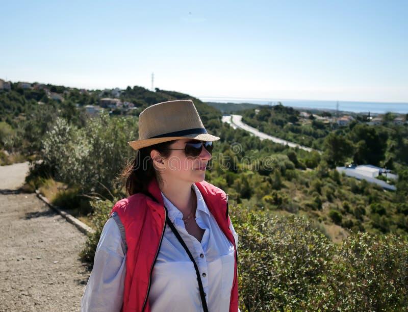 Junger hübscher Brunette mit einem Hut und Glasblicke auf die umgebende Landschaft lizenzfreies stockfoto