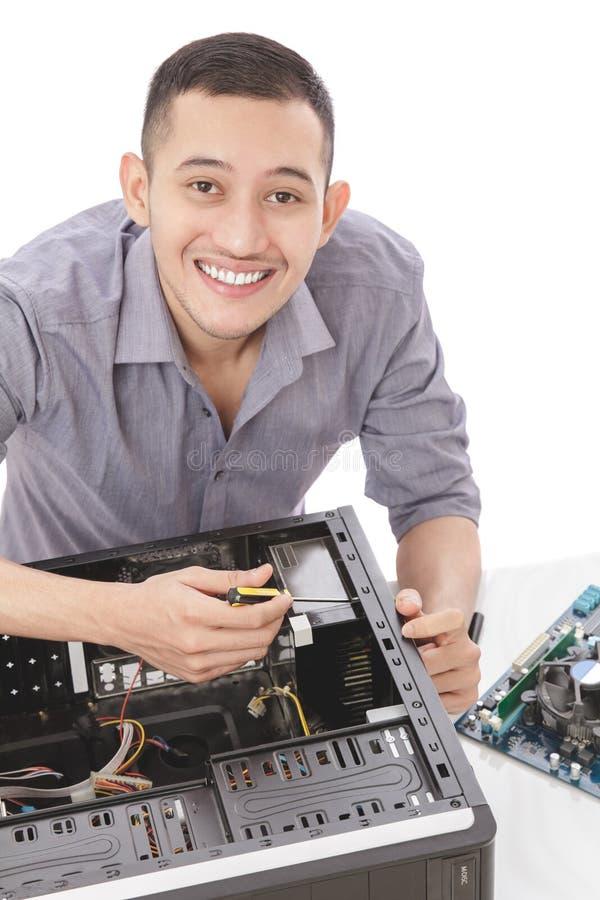 junger hübscher Computerspezialist, der Computer repariert stockfotografie
