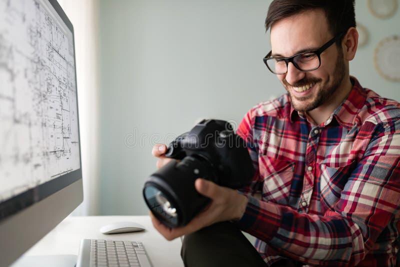 Junger hübscher Designer, der an Projekt auf Computer arbeitet lizenzfreie stockbilder
