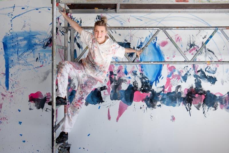 Junger hübscher Frauenmaler hängt am mobilen Baugerüst gegen eine gemalte Wand lizenzfreie stockbilder