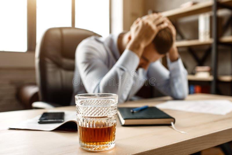 Junger hübscher Geschäftsmann bei Tisch sitzen und unter Kater in seinem eigenen Büro leiden Er hält Hände auf Kopf Glas von lizenzfreie stockfotos