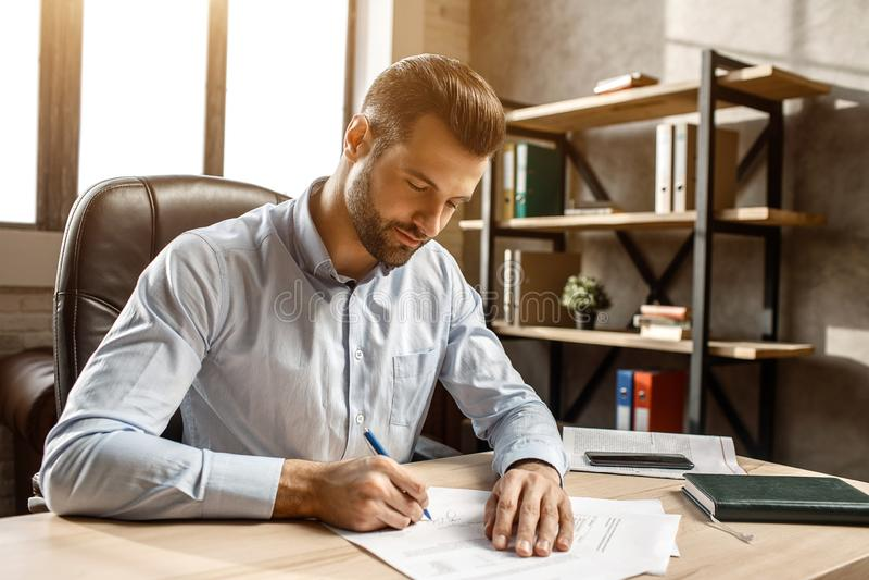 Junger hübscher Geschäftsmann, der bei Tisch in sein eigenes Büro sitzt und schreibt Er setzte Unterzeichnung auf Dokumente Workt stockfotografie