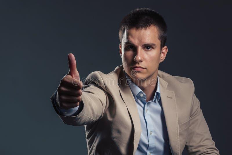 Junger hübscher Geschäftsmann, der sich Daumen zeigt Die goldene Taste oder Erreichen für den Himmel zum Eigenheimbesitze stockbild
