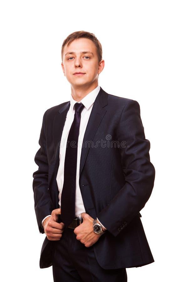Junger hübscher Geschäftsmann im schwarzen Anzug steht gerade, die Ganzaufnahme, die auf weißem Hintergrund lokalisiert wird lizenzfreie stockfotografie