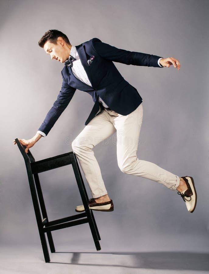 Junger hübscher Geschäftsmann im Studio mit Stuhl stockfotos