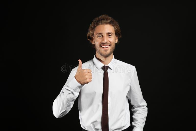 Junger hübscher Geschäftsmannvertretungsdaumen-oben auf schwarzem Hintergrund lizenzfreie stockbilder