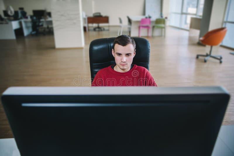 Junger hübscher Hippie-Programmierer, der bei einem Großrechnermonitor und -arbeit sitzt Arbeitsflussbüro lizenzfreie stockfotos