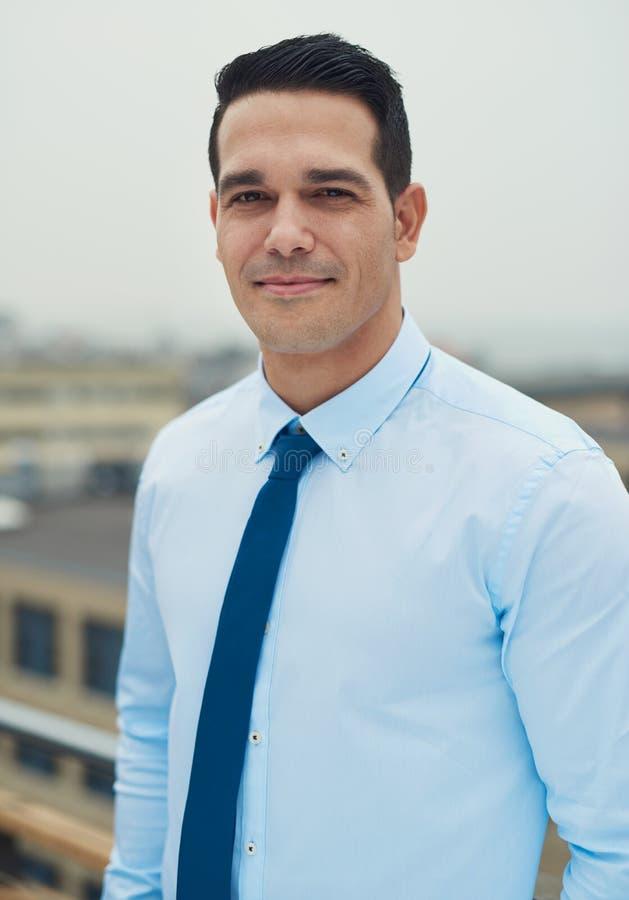 Junger hübscher hispanischer Mann auf einer Dachspitze stockfoto