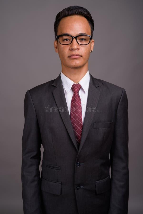 Junger hübscher indischer Geschäftsmann gegen grauen Hintergrund lizenzfreie stockfotografie