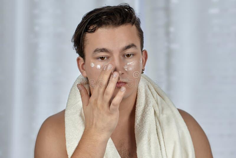 Junger hübscher kaukasischer Mann, der Creme unter den Augen, Tuch auf Schultern aufträgt Interessierendes Gesicht, tägliches Pro lizenzfreie stockfotografie