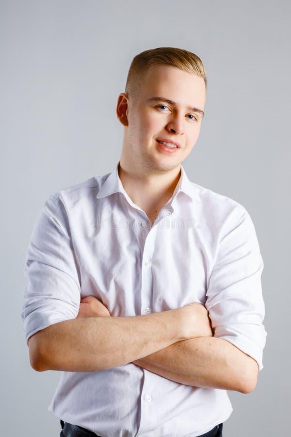 Junger hübscher kaukasischer Mann im weißen Hemd lächelt lizenzfreie stockfotos