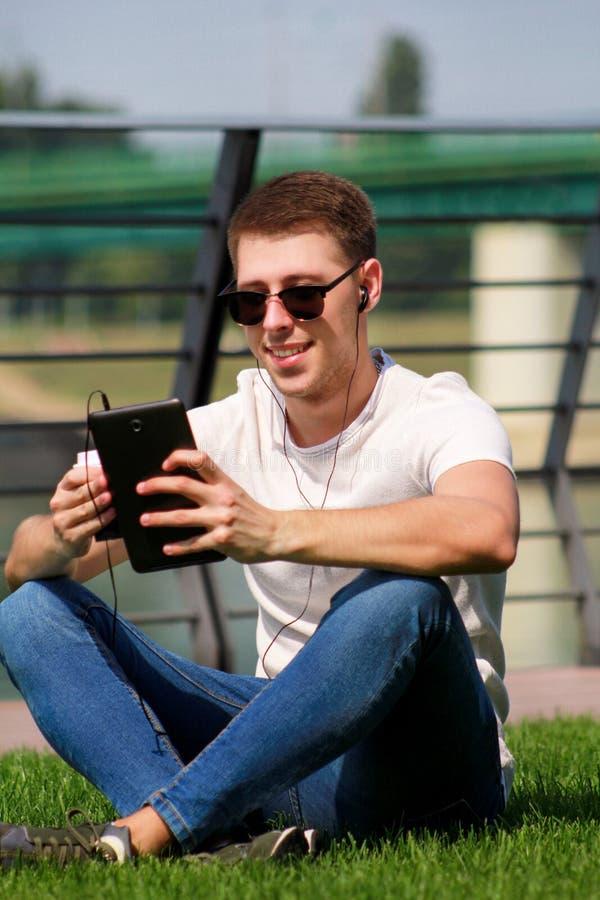 Junger hübscher Kerl mit Sonnenbrille unter Verwendung der Tablette und der Kopfhörer, trinkender Kaffee zum Mitnehmen, bemannen  lizenzfreie stockfotografie