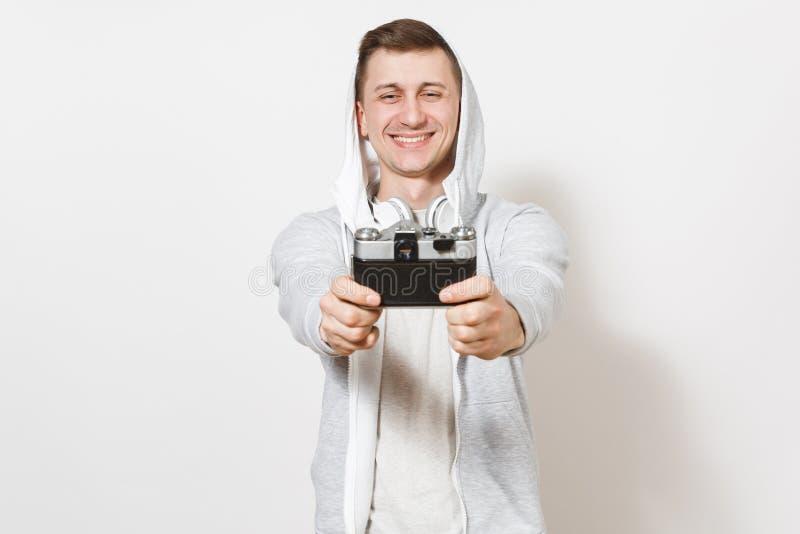 Junger hübscher lächelnder Mannstudent im T-Shirt und im hellen Sweatshirt mit Haube mit Kopfhörern fotografiert sich an stockfotografie