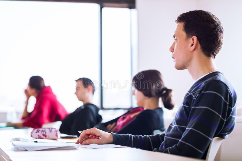 Junger, hübscher männlicher Student, der in einem Klassenzimmer sitzt stockbild