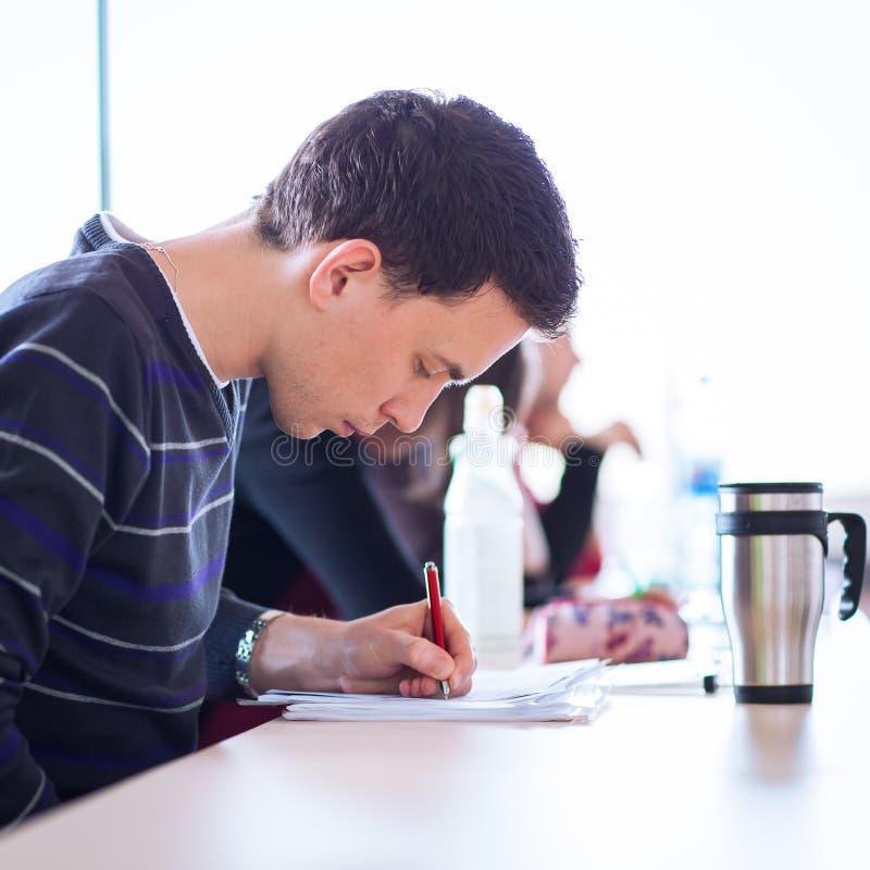 Junger, hübscher männlicher Student, der voll in einem Klassenzimmer sitzt stockbilder