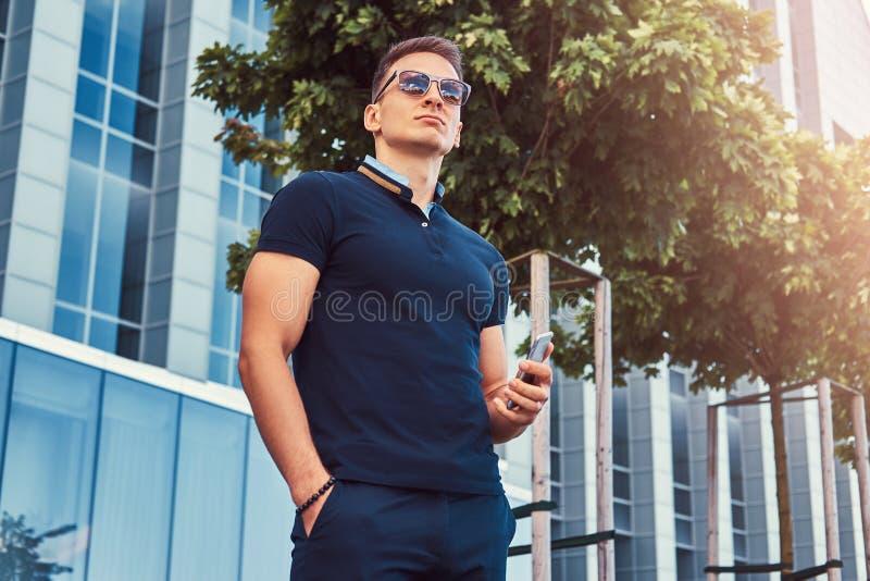 Junger hübscher moderner Mann mit einem stilvollen Haarschnitt in der Sonnenbrille, gekleidet in einem schwarzen T-Shirt und in H lizenzfreie stockfotos