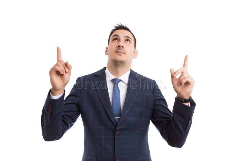 Junger hübscher Verkäufer oder Geschäftsmann, die oben zeigen und schauen stockfotos