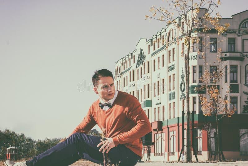 Junger hübscher zufälliger Mann, der auf dem Bürgersteig in alter Stadt a sitzt stockfoto